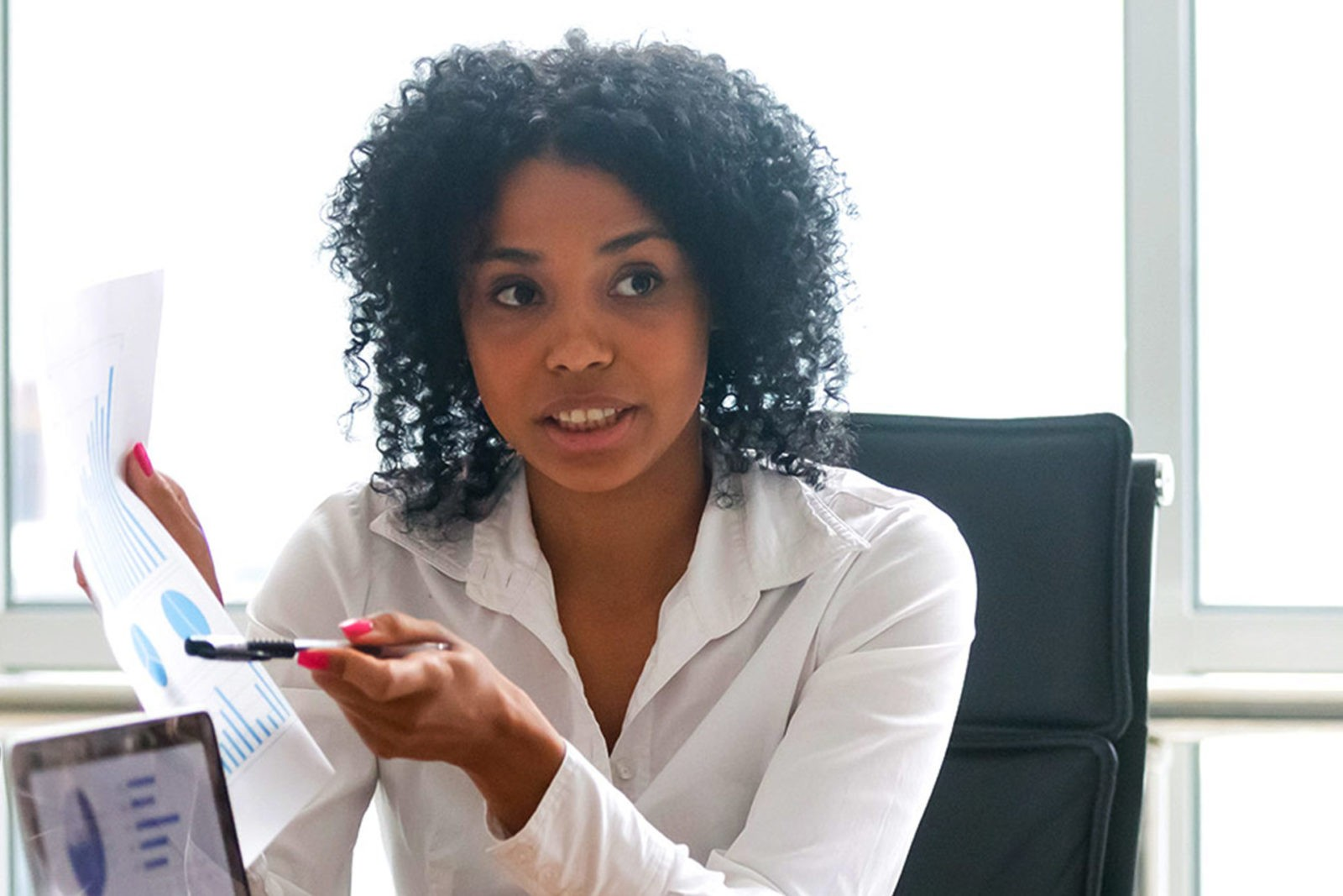 Business woman sitting at desk and pointing to flow chart