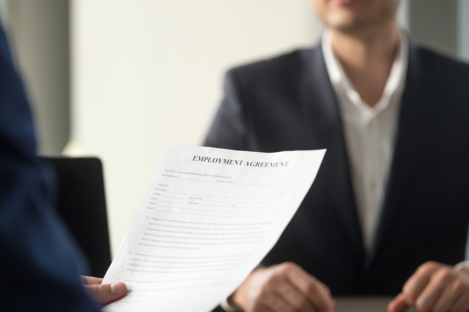 Applicant holding employment agreement in office interview setting.