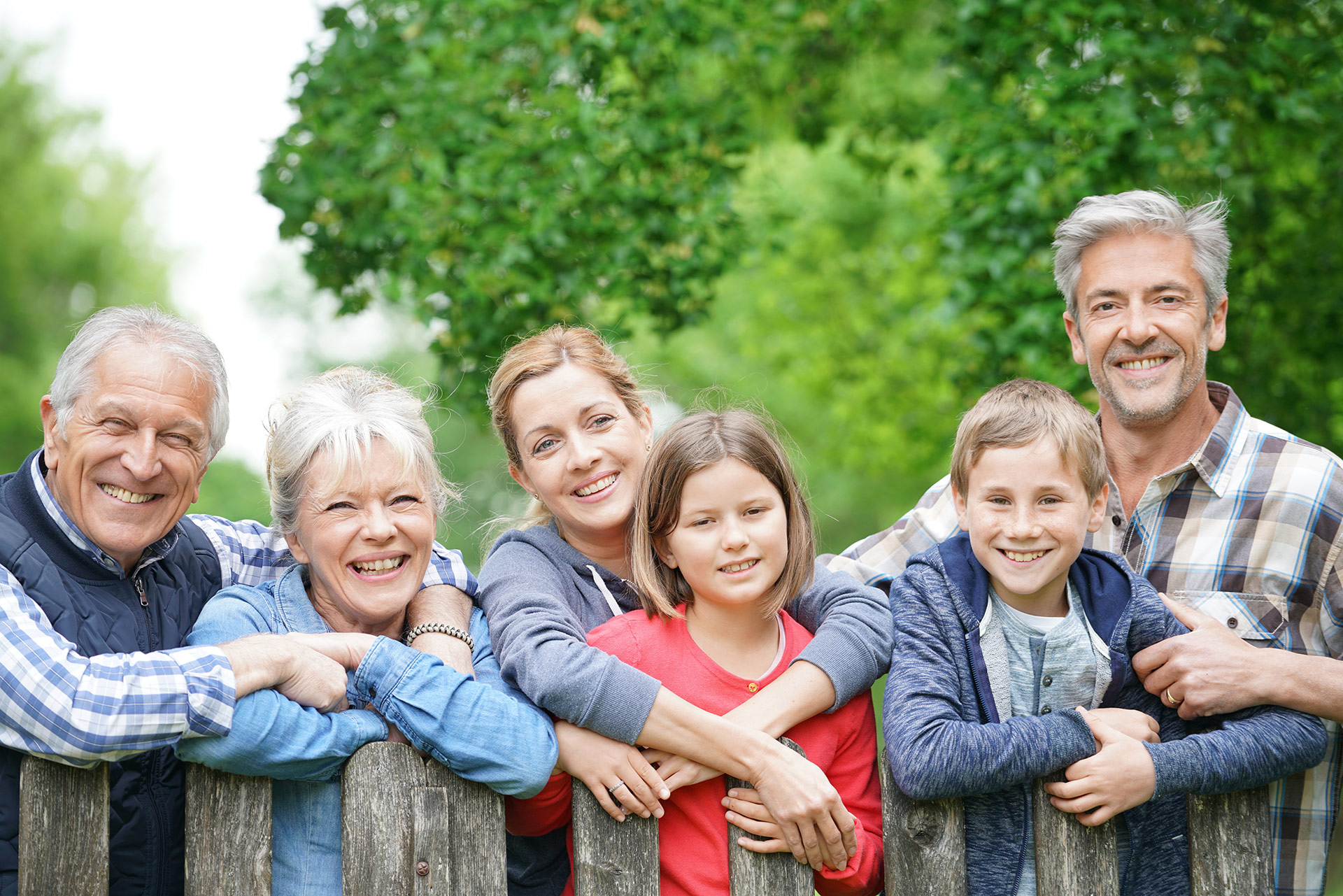 Happy family of children, parents, and grandparents leaning on fence.